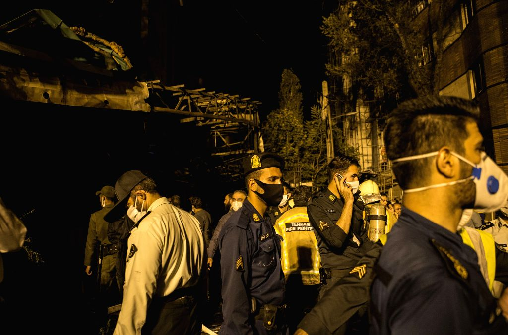 Policemen and firefighters work at the explosion site in Tehran, Iran, June 30, 2020. At least 19 people were killed in an explosion at a clinic in the northern ...