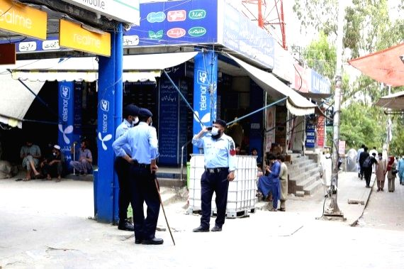 Policemen are on duty at a market to ensure newly imposed government restrictions in Islamabad, capital of Pakistan, on May 8, 2021.