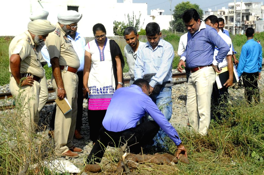 Policemen carry out investigations at the site where rusted bombs were recovered near Chheharta-Attari railway line in Chheharta area of Amritsar on Oct 8, 2016.