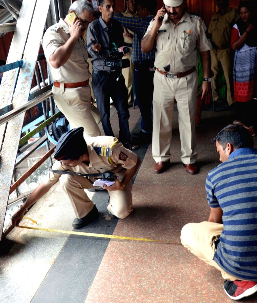 Policemen carry out investigations on a narrow railway footover bridge where a stampede broke out killing at least 22 commuters in Mumbai, on Sept 29, 2017.