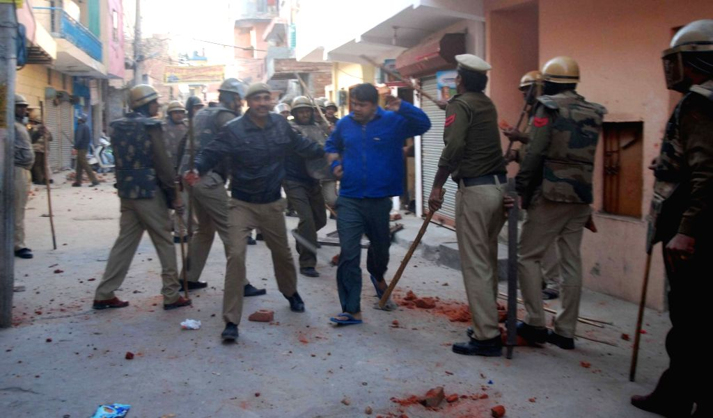 Policemen charge batons after violence broke out during demolition drive of illegal encroachment on govt. land by villagers at sector-19 near village Daultabad in Faridabad on Nov 26, 2016.