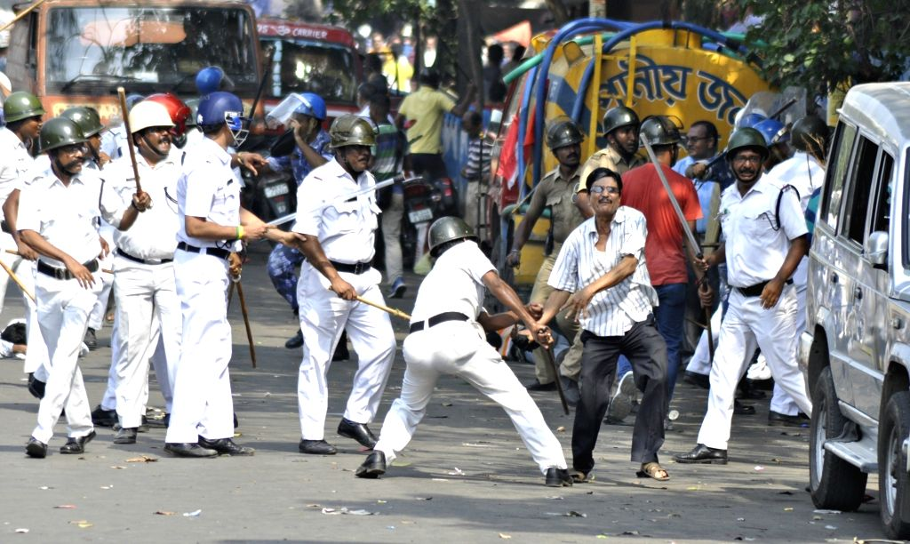 Policemen charge lathis on workers of parties affiliated to the Left Front during a protest after a number of Left Front MLAs including its legislature party leader Sujan Chakraborty were ... - Sujan Chakraborty
