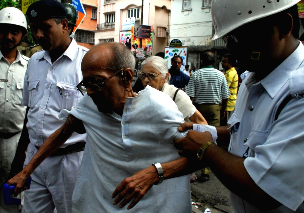 Policemen helping an aged person to reach to the vote booth in Kolkata on 13th May 2009.
