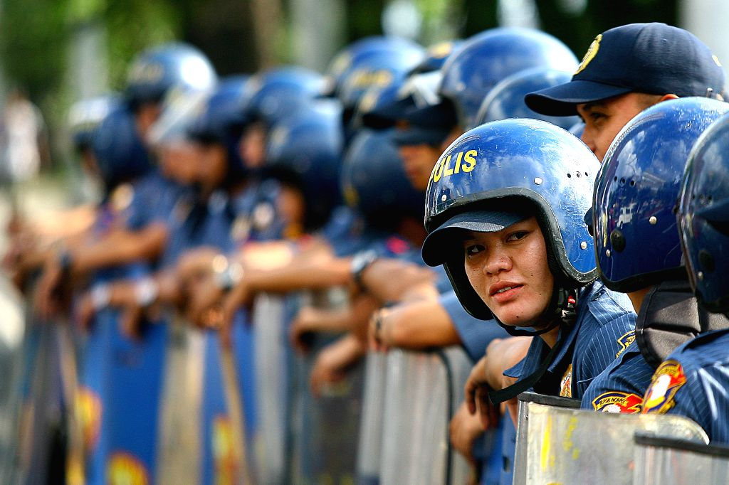 Policemen hold their truncheons and sheilds as they block activists during a protest rally in front of the U.S. Embassy in Manila, the Philippines, Jan. 14, 2016. ...