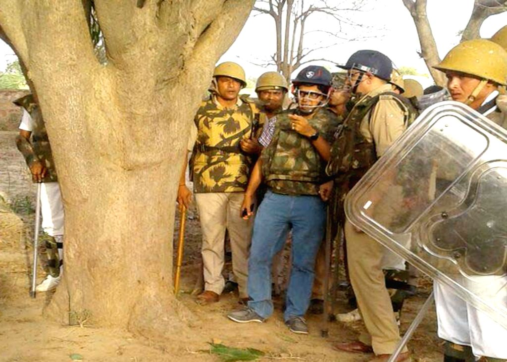 Policemen in action after violence broke out between police and the encroachers who were being evicted from Jawaharbagh in Mathura on June 2, 2016.