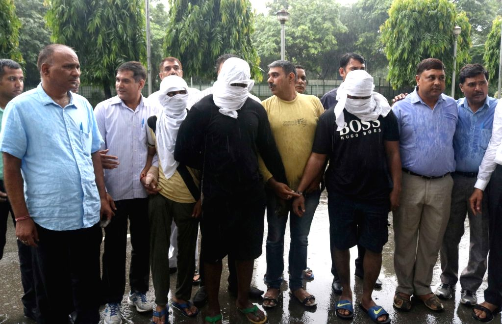 Policemen present before press members of a cheating module active across India at Delhi Police headquarters in New Delhi on July 30, 2016. Five persons including four Neigerian nationals ...
