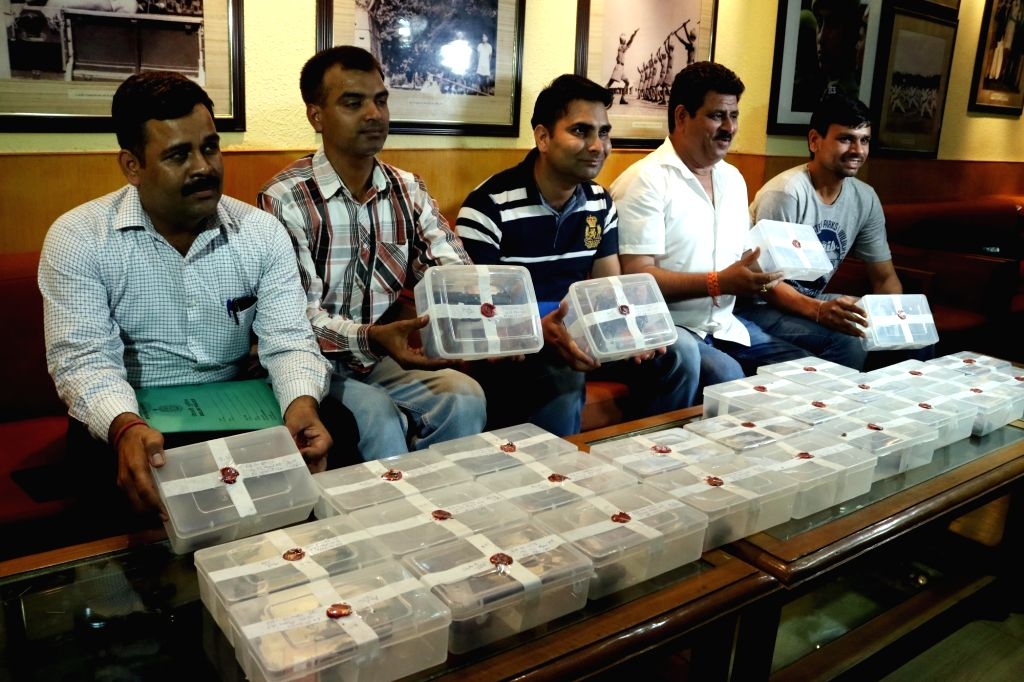 Policemen present before press the confiscated arms, in New Delhi on June 4, 2016.