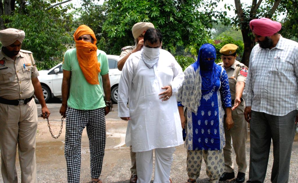 Policemen present before press the smugglers arrested with 1 kg heroin and one Pak sim card in Amritsar on July 30, 2016.