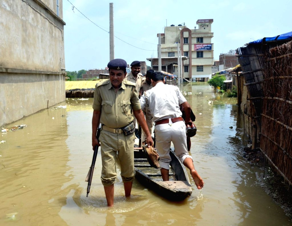 Policemen seen on a boat in front of a police station in Ahiyapur of Bihar's Muzaffarpur on July 18, 2019.
