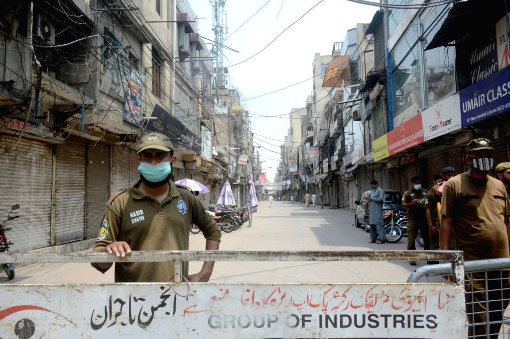 Policemen stand guard at a closed market during lockdown in eastern Pakistan's Lahore on July 30, 2020.
