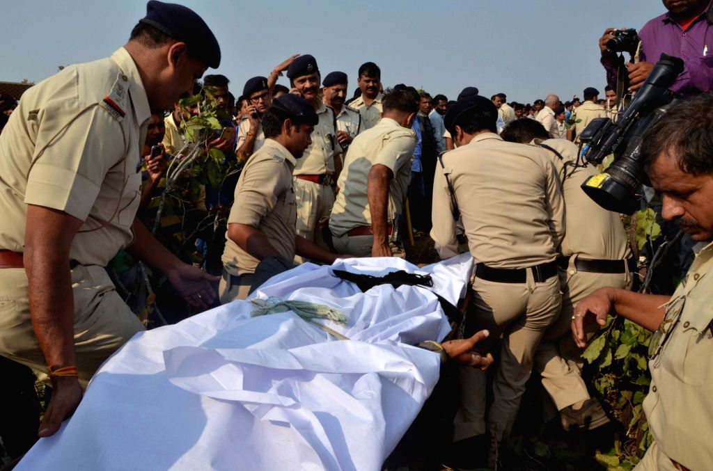 Policemen take away body of one of the eight terrorists of the banned Students Islamic Movement of India (SIMI) who escaped from Bhopal Central Jail and were killed in a gunfight with police ...