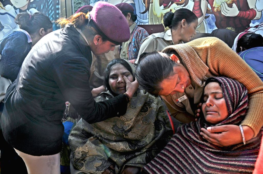 Policewoman console the grief struck relatives of those killed in Bawana factory fire in New Delhi, on Jan 21, 2018. As many as 17 people, including 10 women, were burnt to death or ...