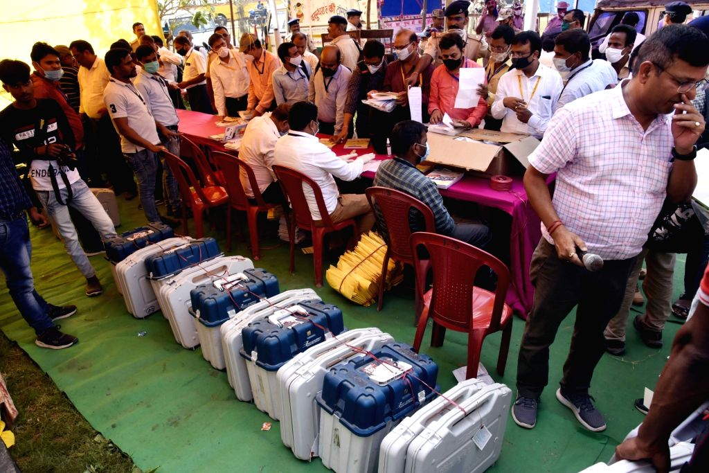 Polling officers receive EVM machines and other polling material as they leave for their respective polling stations on the eve of the Bihar Assembly elections, at Pali in Patna on Oct 27, ...