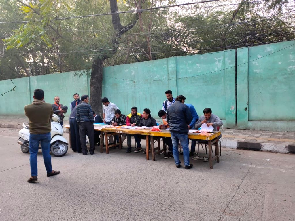 Polling official assist voters at a polling station at Civil Lines during Delhi Assembly elections 2020, on Feb 8, 2020.