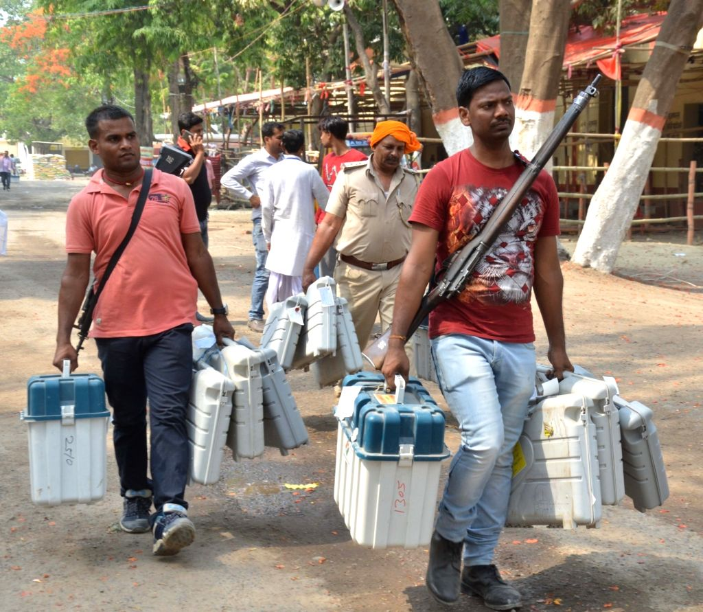 Polling officials and security personnel carrying the Electronic Voting Machine (EVMs) and other necessary inputs required for 2019 Lok Sabha elections, leave for their respective ...