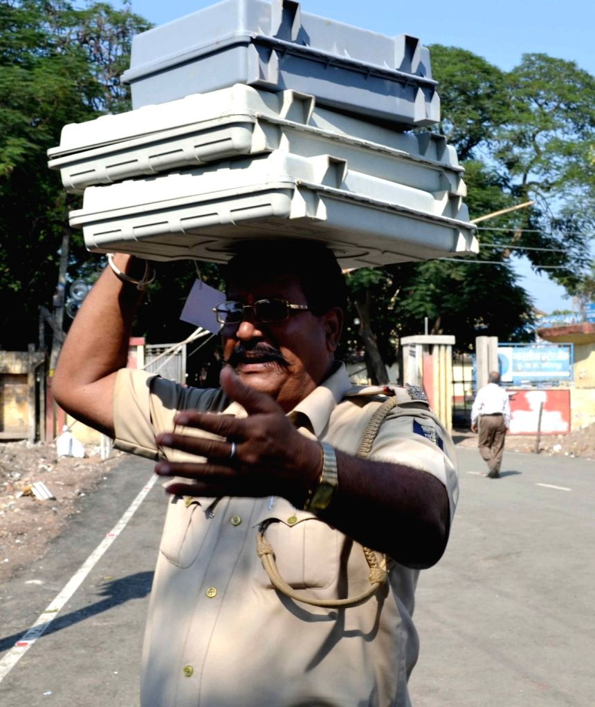 Polling officials and security personnel take Electronic Voting Machines (EVMs) for counting at a counting centre in Muzaffarpur on Oct 31, 2015.