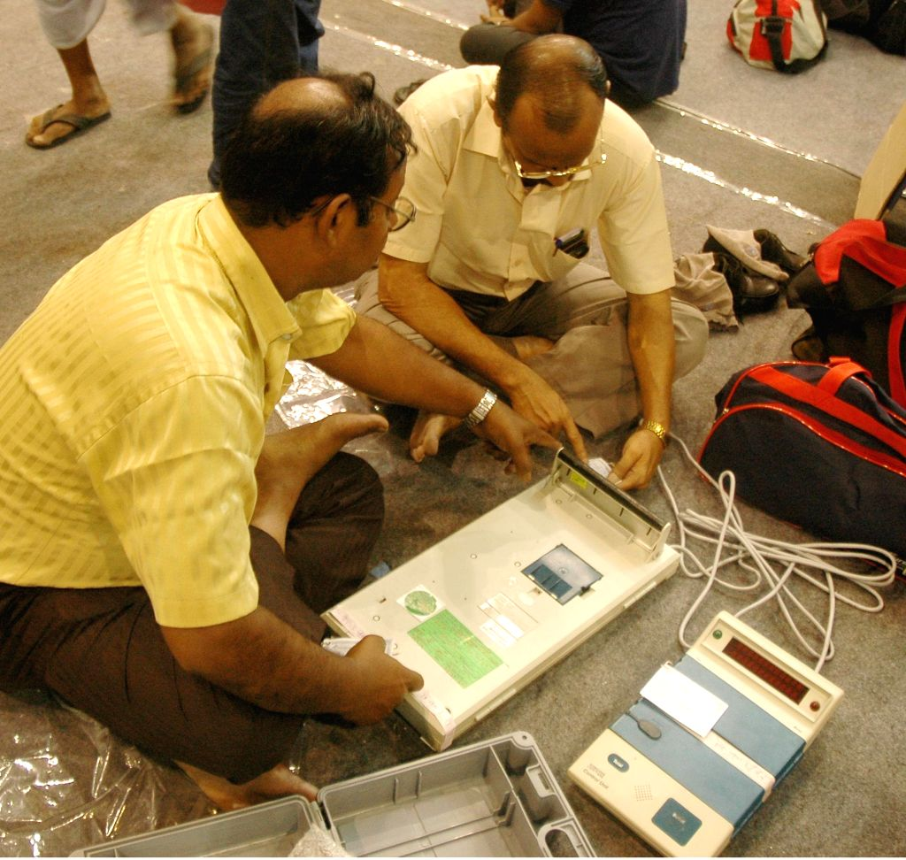 Polling officials busy checking EVM at an EVM distribution center ahead of bypolls to the Chowringhee assembly constituency in Kolkata on Sept 12, 2014.