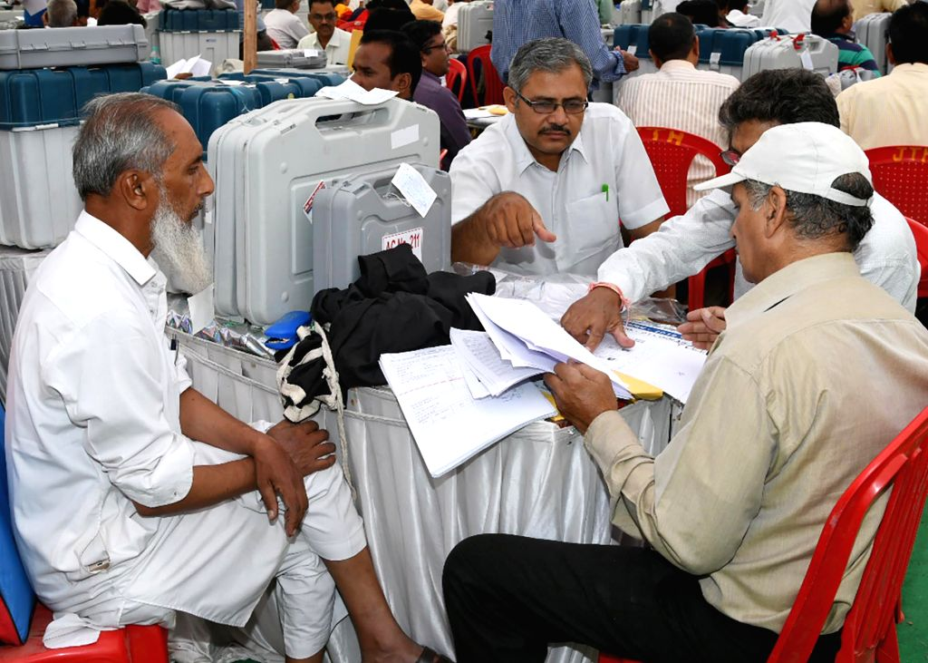 Polling officials busy collecting EVMs and other necessary inputs at the distribution centre on the eve of the final phase of 2019 Lok Sabha elections, in Indore, Madhya Pradesh on May 18, ...