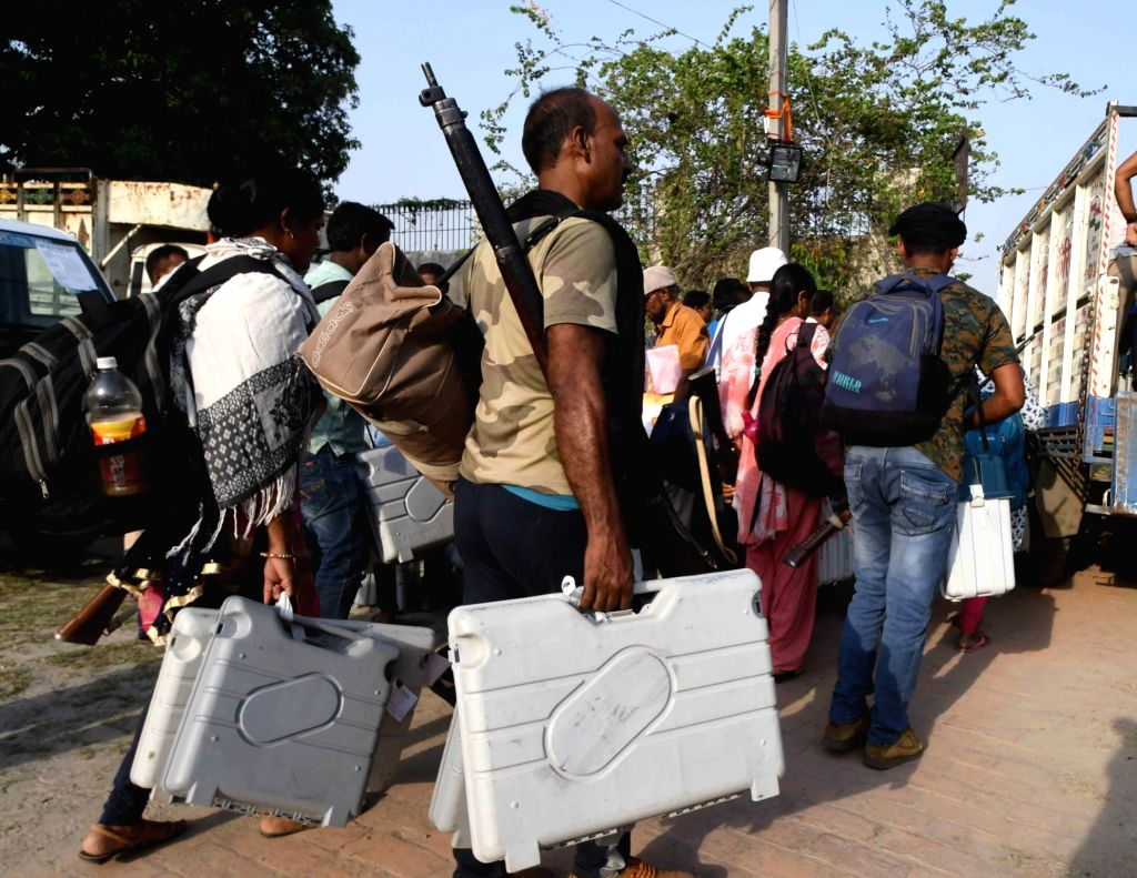 Polling officials carry Electronic Voting Machine (EVMs) and other necessary inputs after collecting them from the distribution centre on the eve of the fifth phase of the 2019 Lok Sabha ...
