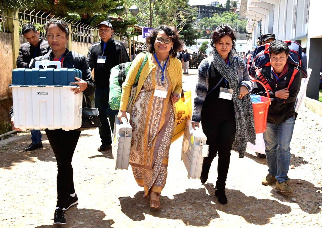 Polling officials carry the Electronic Voting Machine (EVMs) and other necessary inputs required for the 2019 Lok Sabha polls, at the distribution centre, in Shillong, Meghalaya, on April ...