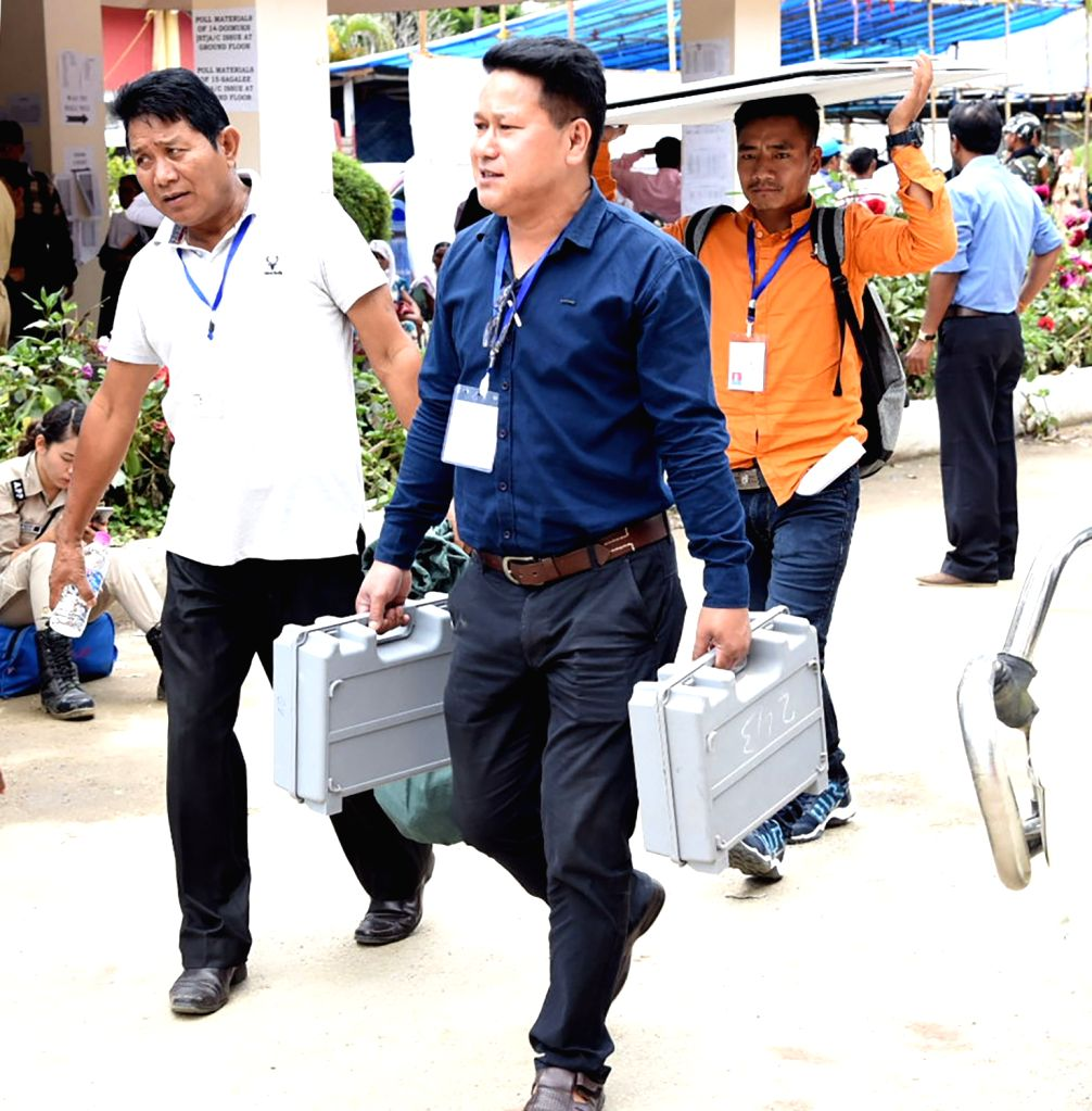 Polling officials carry the Electronic Voting Machine (EVMs) and other necessary inputs required for the 2019 Lok Sabha polls, at the distribution centre, in Itanagar, Arunachal Pradesh, on ...