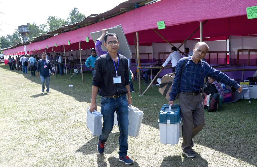 Polling officials carry the Electronic Voting Machine (EVMs) and other necessary inputs required for the 2019 Lok Sabha polls, at the distribution centre, in Assam's Golaghat, on April 10, ...