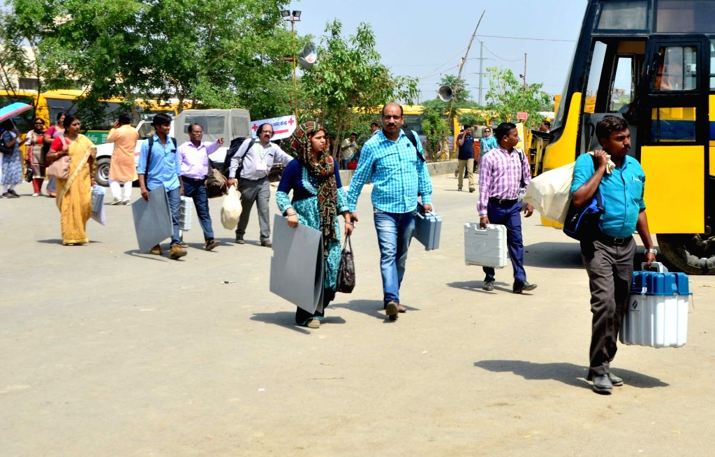 Polling officials carry the Electronic Voting Machine (EVMs) and other necessary inputs required for the 2019 Lok Sabha polls, in Noida, on April 10, 2019. Uttar Pradesh Lok Sabha polls will ...
