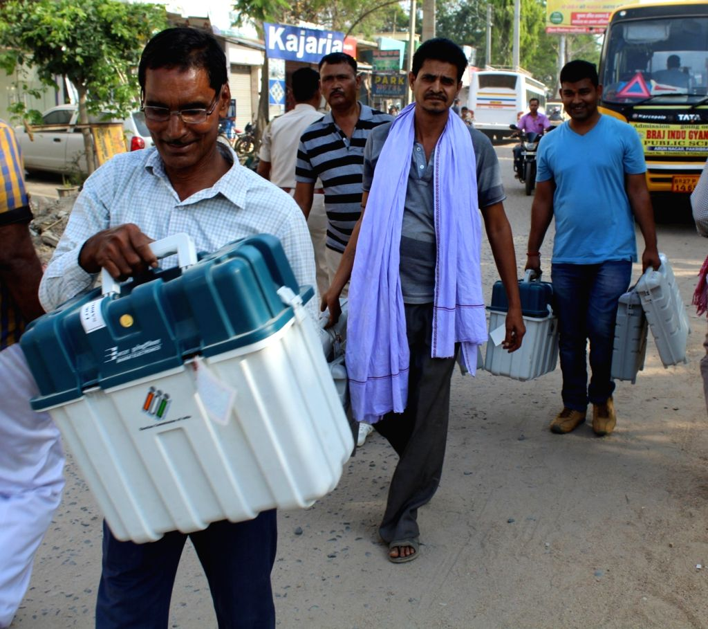 Polling officials carry the Electronic Voting Machine (EVMs) and other necessary inputs required for the 2019 Lok Sabha polls, in Bihar's Nawada, on April 10, 2019. Bihar Lok Sabha polls will ...