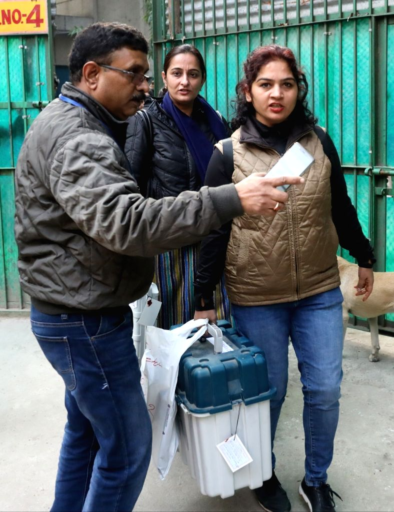 Polling officials carrying the Electronic Voting Machine (EVMs) and other necessary inputs required for the Delhi Assembly Election at a distributions centre in New Delhi on Feb 07, 2020.