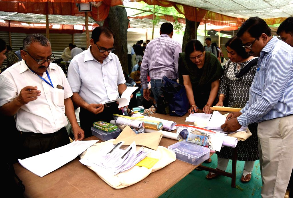 Polling officials check necessary inputs required for the 2019 Lok Sabha elections, at a distribution centre before leaving for their respective polling stations, in New Delhi on May 11, ...