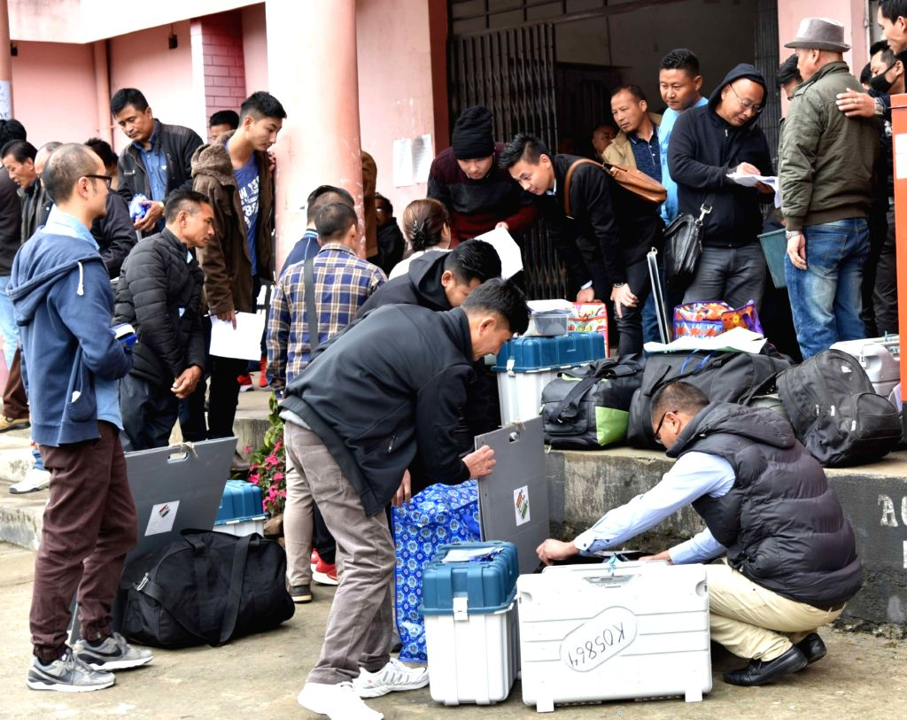 Polling officials check the Electronic Voting Machine (EVMs) and other necessary inputs required for the 2019 Lok Sabha polls, at the distribution centre, in Nagaland's Kohima, on April 10, ...