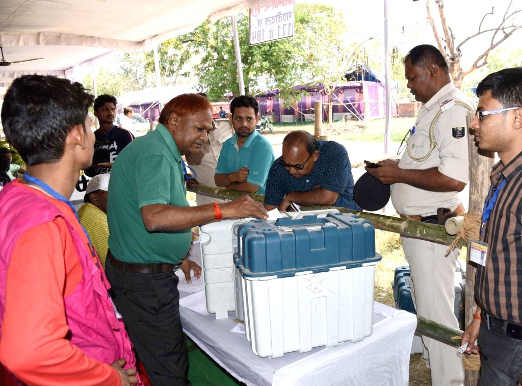 Polling officials check the Electronic Voting Machine (EVMs) and other necessary inputs required for the 2019 Lok Sabha polls, at the distribution centre, in Bihar's Gaya, on April 10, 2019. ...