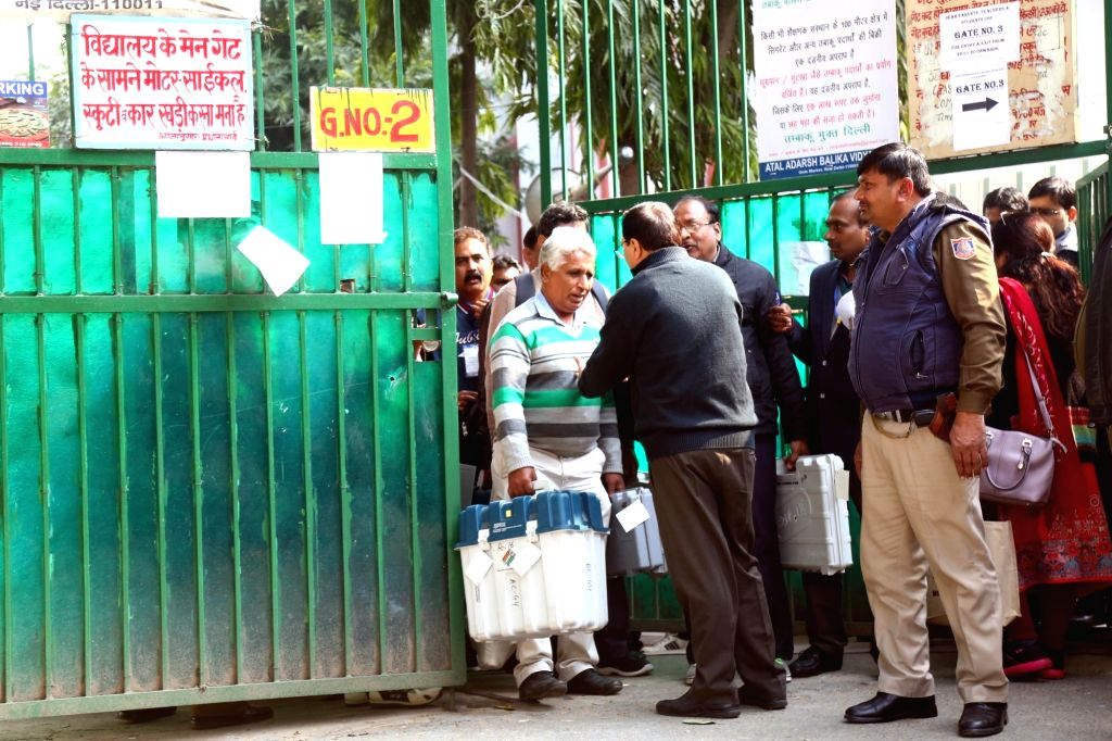 Polling officials checking the Electronic Voting Machine (EVMs) and other necessary inputs required for the Delhi Assembly Election, at a distribution centre in New Delhi on Feb 7, 2020.