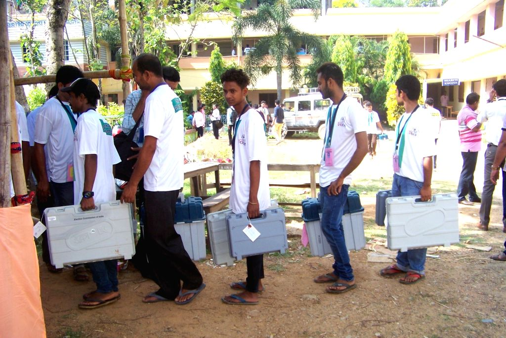 Polling officials leave for their respective polling stations after collecting Electronic Voting Machine (EVMs) and other necessary inputs from the distribution centre ahead of the sixth ...