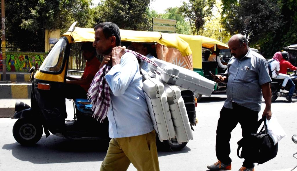 Polling officials leave for their respective polling stations after collecting EVMs and other necessary inputs from the distribution center on the eve of the final phase of 2019 Lok Sabha ...