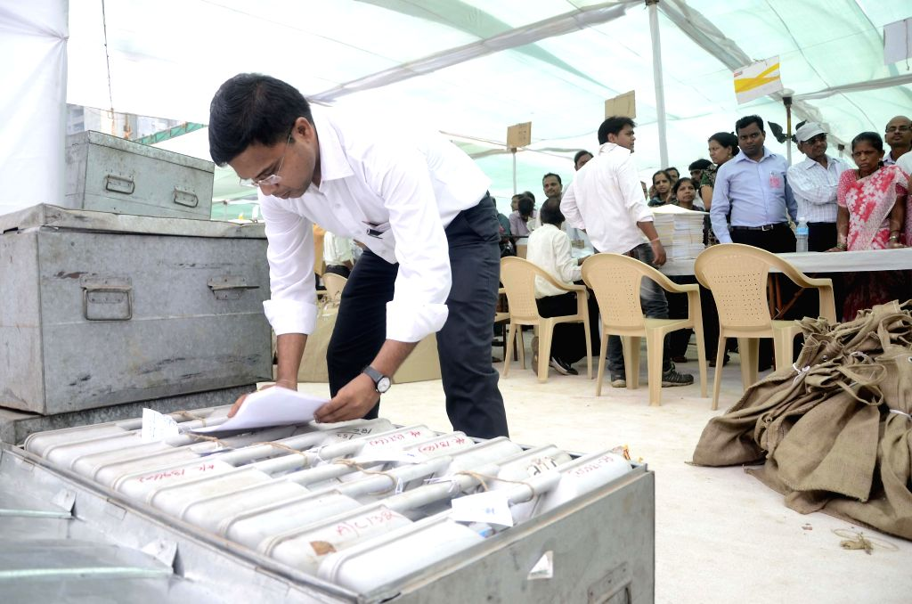 Polling personnel collect their respective Electronic Voting Machines (EVMs) at a polling station before leaving for their respective polling booths ahead of the 6th phase of 2014 Lok Sabha Elections