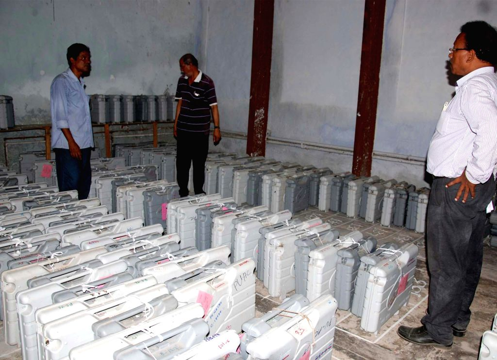 Polling personnel inspect Electronic Voting Machines (EVMs) at a polling station in Puri of Odisha on April 14, 2014. (Photo : Arabinda Mahapatra/IANS)
