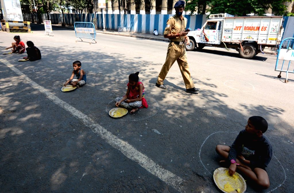 Poor children have food dustributed by the CRPF personnel while practising socal distancing on Day 5 of the 21-day countrywide lockdown imposed to contain the spread of novel coronavirus, in ...