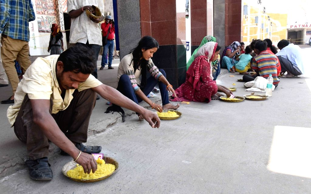 Poor people have food distributed among them by the Railway Protection Force (RPF) personnel at the Patna Junction Railway Station on Day 5 of the 21-day countrywide lockdown imposed to ...