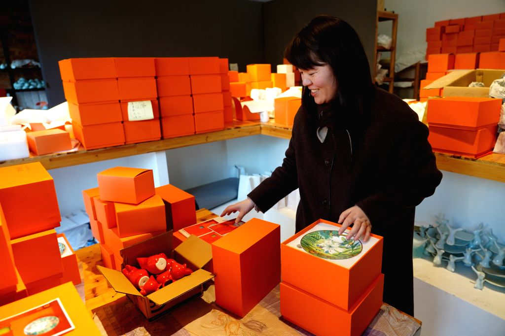 Porcelain-making artist Wu Anran packages her porcelain works in the shape of the rat in Jingdezhen, east China's Jiangxi Province, Jan. 8, 2020. In accordance ... - W