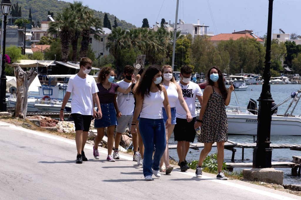 Poros (Greece), Aug. 7, 2020 People wearing face masks walk at the port of Poros island, south of Athens, Greece, Aug. 7, 2020. A continuing surge in the number of confirmed coronavirus ...