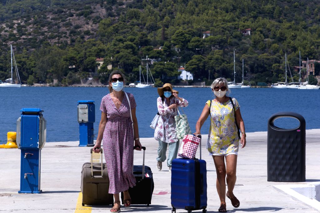 Poros (Greece), Aug. 7, 2020 Visitors wearing face masks are seen at the port of Poros island, south of Athens, Greece, Aug. 7, 2020. A continuing surge in the number of confirmed ...