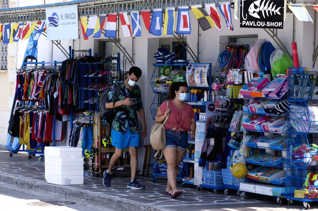 Poros (Greece), Aug. 7, 2020 Visitors wearing face masks walk past shops at the port of Poros island, south of Athens, Greece, Aug. 7, 2020. A continuing surge in the number of confirmed ...