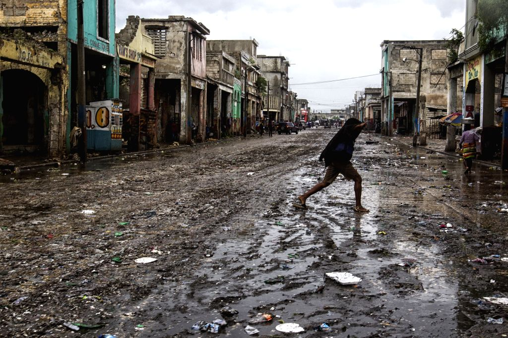 PORT-AU-Image provided by the United Nations Children's Fund (UNICEF) shows a person walking on a street after the arrival of hurricane Matthew, in Port-Au-Prince, ...