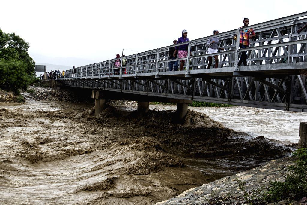 PORT-AU-Image provided by the United Nations Children's Fund (UNICEF) shows people crossing a bridge over the Grise river, after the arrival of hurricane Matthew in ...