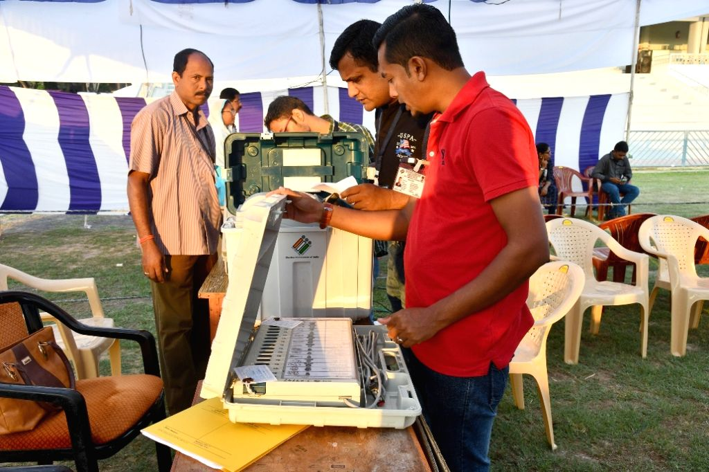 Port Blair: Polling officials check the Electronic Voting Machine (EVMs) and other necessary inputs required for the 2019 Lok Sabha polls, at the distribution centre, in Port Blair, Andaman and ...