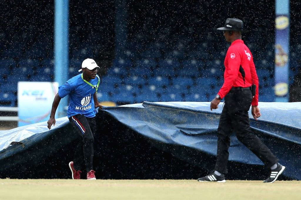 Port of Spain: A groundsman pull on the covers as rain disrupts the 2nd ODI match between India and West Indies at Queen's Park Oval in Port of Spain, Trinidad on Aug 11, 2019.