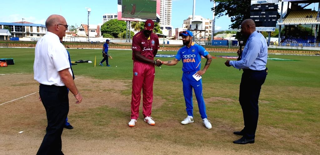 Port of Spain: Indian skipper Virat Kohli and West Indies' skipper Jason Holder during the toss ahead of the 2nd ODI match between India and West Indies at Queen's Park Oval in Port of Spain, ... - Virat Kohli