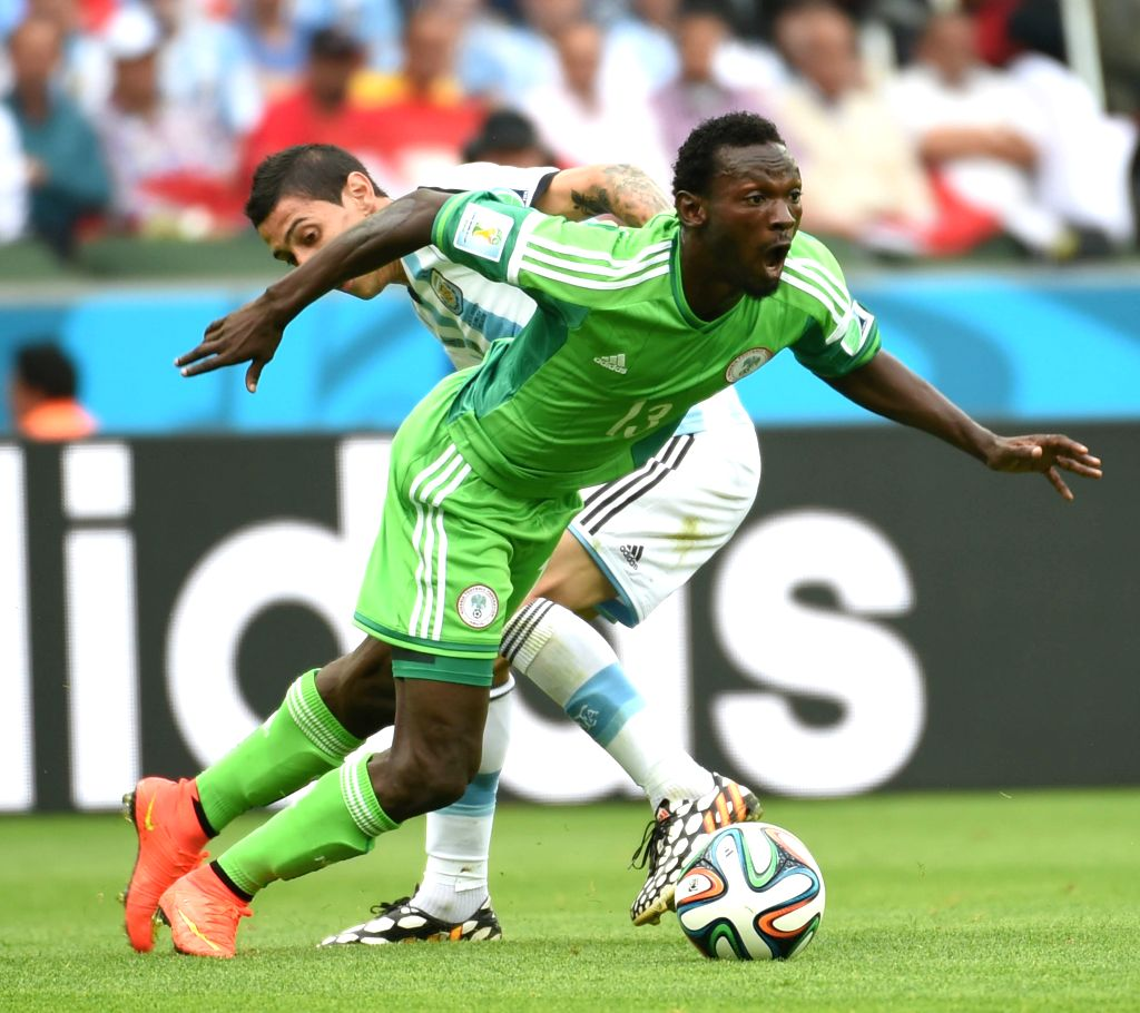 Argentina's Angel Di Maria (back) vies with Nigeria's Juwon Oshaniwa during a Group F match between Nigeria and Argentina of 2014 FIFA World Cup at the Estadio
