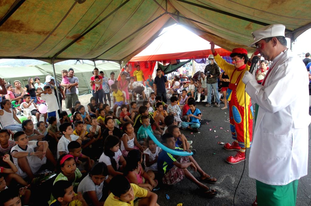 """PORTOVIEJO (ECUADOR), April 22, 2016 Cesar Macias (R), known as the clown """"Lapicito"""", cheers up the children that stay in a shelter installed after the earthquake at Tamarindos ..."""